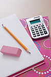 Pencil and calculator on notebook