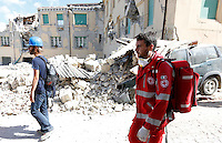 An operator of the Italian Red Cross walks past rubble of collapsed buildings in the village of Amatrice, central Italy, hit by a magnitude 6 earthquake at 3,36 am, 24 August 2016.<br /> Un operatore della Croce Rossa cammina tra le macerie degli edifici crollati dopo il terremoto che alle 3,36 del mattino ha colpito Amatrice, 24 agosto 2016.<br /> UPDATE IMAGES PRESS/Riccardo De Luca