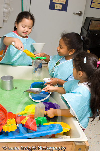 Preschool children ages 3-4 group of girls at water table wearing smocks cooperative play vertical