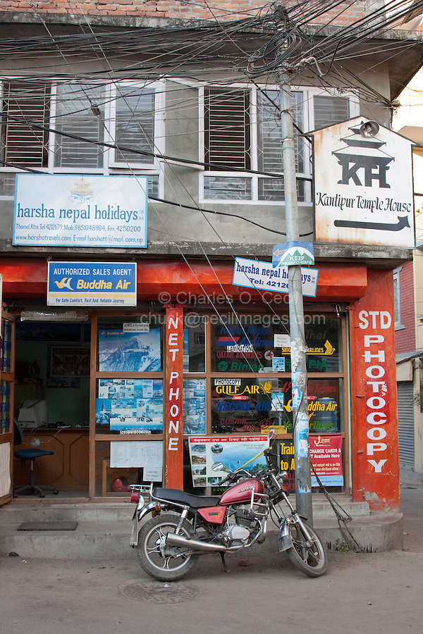 Kathmandu, Nepal.  Street Scene, Motorcycle in front of Travel Agency.  Electric wiring suggests that electrical service has grown in a jury-rigged manner over time, with no master plan.