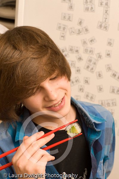 Teenage boy 14 years old food snack holding piece of avocado sushi in pair of chopsticks vertical Caucasian
