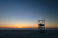 Person watches the sunrise over the ocean, Nauset Beach, Cape Cod National Seashore, Cape Cod, Massachusetts, USA