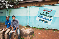 Nigeria. Enugu State. Enugu. Army Day Secondary School ( Awkunanaw in Igbo language). Two Igbo students sit on a rock outside school. On the wall, the written words: Avoid malpractices - Homosexualism - Lesbianism. Sexism is a prejudice or discrimination based on a person's sex or gender. The Army Day Secondary School was inaugurated in October 1998. Enugu is the capital of Enugu State, located in southeastern Nigeria. 11.07.19 © 2019 Didier Ruef