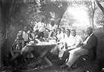 BACKYARD PICNIC. In a backyard enclosed with a picket fence, 10 picnickers (and one pit bull terrier) pause for a toast before their meal. The scene appears casual, but the picnic benches have been angled out from the table to allow each person to be seen, and to lead the eye to the couple serving as host and hostess<br /> <br /> INFORMATION CONTRIBUTED BY STAN SCHMUNK 8/20/2018: The first gent seated on the left is William David Black who owned a home at 708 N. 13 st. He was born in 1876 in Mississippi where his parents had been slaves. In 1908 he married Ella Goodlow in Grand Island, Ne. In 1910 he was shown as a worker in a stone quarry in Weeping Water. By 1920 he owned a little home in Lincoln and was working as a barber. By 1925 his wife was a widow. I found no info on what happened to William. The couple had numerous children. The two young men seated on the right who look like each other and William are Theodore the older and Harry the younger. The widow moved east to live near 24th & Q where she also owned the home. She died in 1937 and is buried in Wyuka. I think she may be the woman seated next to William but can't be sure. At least two of the children ended up in Los Angeles and are buried there. <br /> <br /> Photographs taken on black and white glass negatives by African American photographer(s) John Johnson and Earl McWilliams from 1910 to 1925 in Lincoln, Nebraska. Douglas Keister has 280 5x7 glass negatives taken by these photographers. Larger scans available on request.
