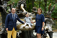 Portrait of mom & dad with their six year old daughter at the Alice in Wonderland Statue in Central Park.