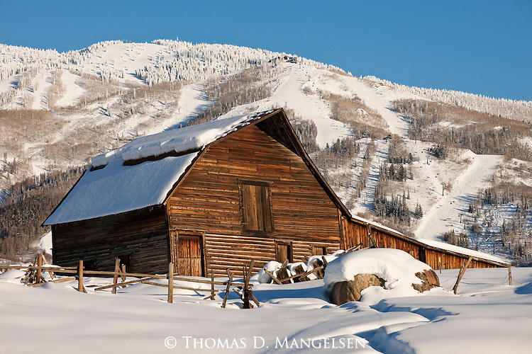 Below the Stemboat ski hill in Colorado, the late afternoon sun highlights the iconic Steamboat barn and a meandering path leading to it.