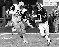 David Boone Hamilton Tiger Cats chases Ottawa Rough Riders quarterback Tom Clements 1976. Copyright photograph Scott Grant