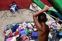 A young Colombian mother with her babygirl sells rummage and used clothes from garbage dumps in the slum of Calvario, Cali, Colombia, 3 April 2004. Calvario, a slum right in the centre of the city, is considered the social bottom of Cali society. Poor dwellers recollect the garbage in the near city centre to sell it for recycling, while their children get high by sniffing the shoe glue on the dirty streets of ghetto. The order in Calvario is maintained by the illegal authorities, usually former policemen or army members, who set their own rules. Criminality, drug abuse, unemployment never allow the slum people jump off the misery and stop being the second category citizen within the rigid society of Colombia. Although Christian missionary organizations attempt to provide help, the overall situation does not improve.
