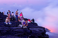 EDITORIAL ONLY. Spectators watch as lava flows into the sea. Hawaii Volcanoes National Park, Big Island