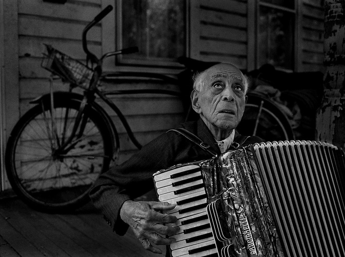 Jacob Brown, the last living member of what had been a thriving black enclave in the otherwise lilywhite town of Fair Haven N.J. plays on his accordian outside his small disheveled home which is tucked in behind new suburdan homes. Photo by Peter Ackerman, Asbury Park Press