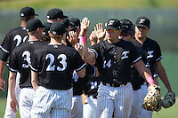 Corey Zangari (14) of the Kannapolis Intimidators high fives teammates following their win over the Lakewood BlueClaws at Kannapolis Intimidators Stadium on May 8, 2016 in Kannapolis, North Carolina.  The Intimidators defeated the BlueClaws 3-2.  (Brian Westerholt/Four Seam Images)