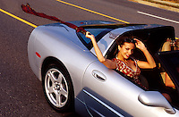 A smiling young woman lets her scarf blow in the wind as she rides in a silver Corvette convertible.