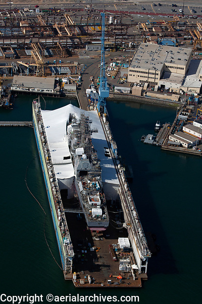 aerial photograph of a Navy destroyer for maintenance in the BAE Systems Repair drydock, San Diego, California; scaffolding covers much of the ship