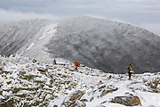 Backcountry campers travel along the Bondcliff Trail on the summit of Bondcliff in the Pemigewasset Wilderness of the New Hampshire White Mountains on a cloudy winter day.