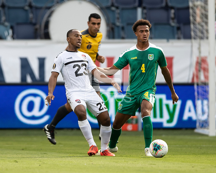 KANSAS CITY, KS - JUNE 26: Leston Paul #23 and Elliot Bonds #4 go for the ball during a game between Guyana and Trinidad