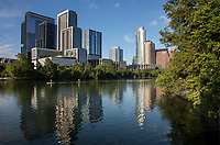 Stand up paddle boarders (SUP) glide past the ever expanding Austin skyline on Lady Bird Lake during a beautiful sunny afternoon in downtown Austin, Texas.