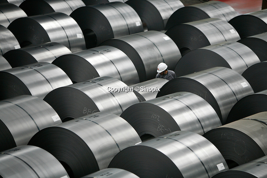 A worker inspects and marks rolls of steel plates at Ma Steel (Maanshan Iron & Steel Co.) in Maanshan, Anhui Province, China..10 Apr 2006