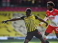 24th April 2021; Vicarage Road, Watford, Hertfordshire, England; English Football League Championship Football, Watford versus Millwall; Ismaïla Sarr of Watford is taken down by Mahlon Romeo of Millwall but the referee waves play on.
