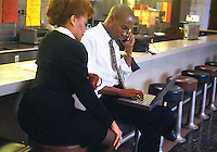 Working on a project outside of the office. Businessman and businesswoman working at laptop computer and talking on cell phone while sitting in a diner. Business people. Denver Colorado United States Diner.