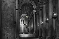 A view down a Vatican hallway in Rome in black and white with a hint of colour in the main light.