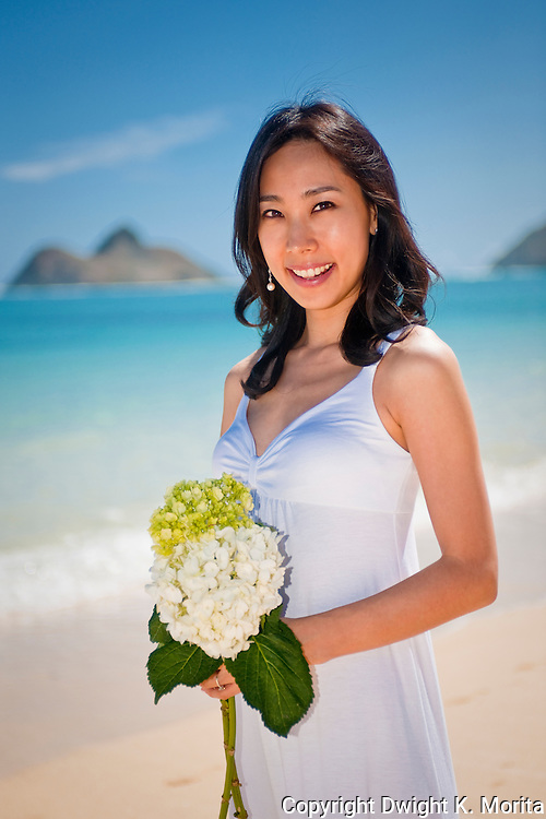 Asian bride poses with bouquet of flowers during honeymoon on Lanikai Beach, Kailua, Hawaii