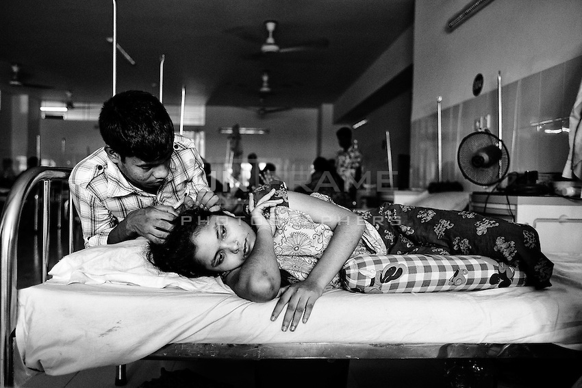 18 years old garments worker Sonia with her husband at Anam Medical College Hospital.  Sonia had her right leg amputated to free her from the rubble when she was rescued nearly 48 hours after the building collapsed. Savar, near Dhaka, Bangladesh