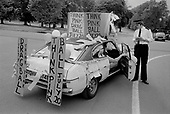 Police officer and a car with placards advertising a drag ball on the London Gay Pride march,1979