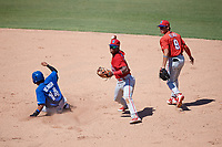 Philadelphia Phillies shortstop Luis Garcia (5) throws to first base in front of Luis Rojas (9) as Steward Berroa (14) slides into second base during a Florida Instructional League game against the Toronto Blue Jays on September 24, 2018 at Spectrum Field in Clearwater, Florida.  (Mike Janes/Four Seam Images)