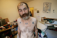 Switzerland. Geneva. Poverty in Geneva. Fredo, 46 years old, is a swiss citizen. He is unemployed and lives from social welfare. He is at home in his small and messy rented flat. He is stripped to the waist and shows his various tattoos on his body. Model Released.  © 2005 Didier Ruef