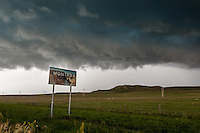 Montana sign beneath a stormy sky at the Montana state line