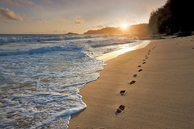 Sunrise at Secret Beach with footprints in the sand, Kauai, Hawaii.