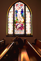 Man praying in the pew of a church.