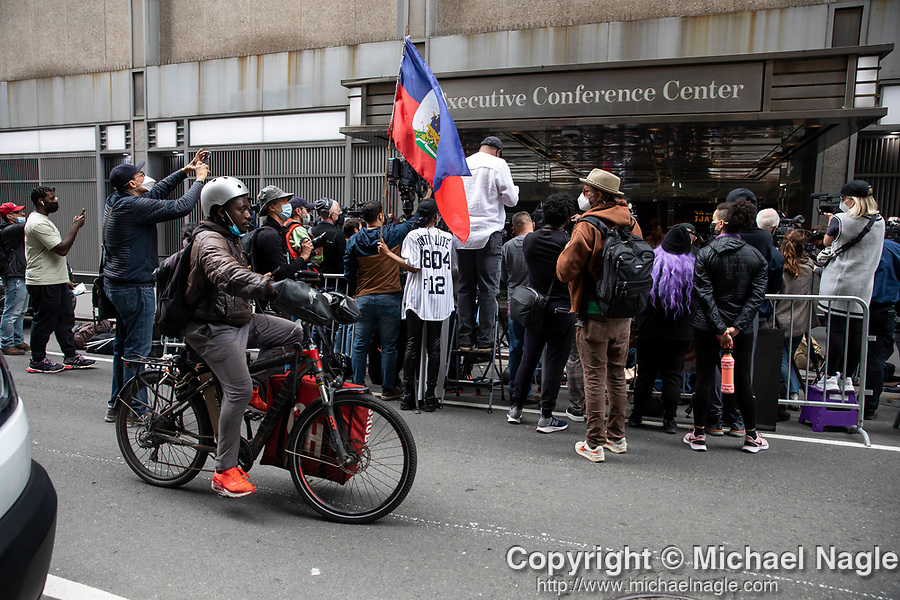 """A bike messenger passes a press conference held by Reverend Al Sharpton in response to the George Floyd and Duante Wright cases along with Benjamin Crump, attorney for the Wright family, and members of the """"Mother's of the Movement"""" during the National Action Network (NAN) Virtual Convention 2021 in New York on Wednesday, April 14, 2021. Photograph by Michael Nagle"""