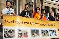 """Protest gegen den syrischen Diktator Bashar al-Assad.<br /> Am Freitag den 21. August 2015 protestierten mehrere hundert Menschen, die meissten Buergerkriegsfluechtlinge aus Syrien, gegen den fortdauernden Buergerkrieg in ihrem Herkunftsland. Sie gedachten annlaesslich des 2. Jahrestag der Opfer des Giftgas-Angriffs vom 21. August 2013 in Damaskus. Das Assad-Regime hatte ueber 1.600 Menschen mit dem Nervengift Sarin ermordet.<br /> Nach Angaben des deutschen Vertreters der """"Syrischen Nationalen Koalition"""", Dr Bassam Abdullah,  werden in Syrien weiterhin Menschen durch Giftgas durch die Regierungstruppen getoetet. Die Koalition ist ein Zusammenschluss von syrischen Muslimen, Christen, Assyrern und Kurden.<br /> Im Bild: Demonstranten mit einem Banner """"Assad toetet mit Giftgas immer noch!!""""<br /> 21.8.2015, Berlin<br /> Copyright: Christian-Ditsch.de<br /> [Inhaltsveraendernde Manipulation des Fotos nur nach ausdruecklicher Genehmigung des Fotografen. Vereinbarungen ueber Abtretung von Persoenlichkeitsrechten/Model Release der abgebildeten Person/Personen liegen nicht vor. NO MODEL RELEASE! Nur fuer Redaktionelle Zwecke. Don't publish without copyright Christian-Ditsch.de, Veroeffentlichung nur mit Fotografennennung, sowie gegen Honorar, MwSt. und Beleg. Konto: I N G - D i B a, IBAN DE58500105175400192269, BIC INGDDEFFXXX, Kontakt: post@christian-ditsch.de<br /> Bei der Bearbeitung der Dateiinformationen darf die Urheberkennzeichnung in den EXIF- und  IPTC-Daten nicht entfernt werden, diese sind in digitalen Medien nach §95c UrhG rechtlich geschuetzt. Der Urhebervermerk wird gemaess §13 UrhG verlangt.]"""