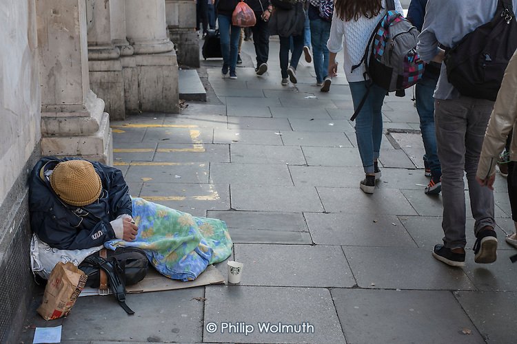 Homeless man sleeping on the street in Holborn London.