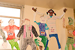Education elementary Kindergarten large colorful human size paper figures done by students hanging on classroom wall showing various physical and personality characteristics horizontal