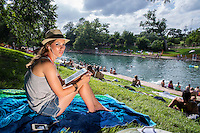 Local Austin woman listens to music with earbuds and surfs the web on a table computer at Barton Springs pool during a hot Texas summer's day.