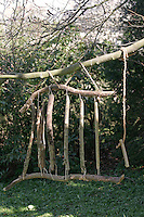 Kinder basteln Klangspiel aus Ästen, Fertiges Klangspiel hängt im Garten an einem Baum
