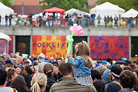 Father giving his daughter, holding a flower ballon, a shoulder ride for a better view of street performers, Northwest Folklife Festival 2016, Seattle Center, Washington, USA.