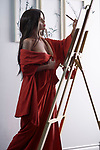 Artistic sensual portrait of a beautiful asian woman in red kimono, Japanese sumi-e artist with an easel, painting in her studio Image © MaximImages, License at https://www.maximimages.com