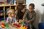 Education Preschool 2-3 year olds female teacher talking with boy and girl about conflict over toy