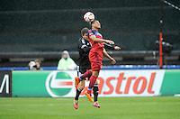 Washington, D.C.- March 29, 2014. Quincy Amarikwa of the Chicago Fire heads the ball against Bobby Boswell (32) of D.C. United. The Chicago Fire tied D.C. United 2-2 during a Major League Soccer Match for the 2014 season at RFK Stadium.