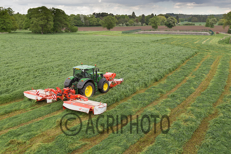 A contractor mowing grass for silage on a Dairy farm with a John Deere 6210R and Kuhn triple mowers<br /> Picture Tim Scrivener 07850 303986