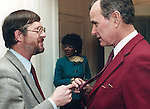 President George H.W. Bush and Ron Bennett White House Photographer check out their ties,
