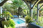 Lush container plantings surround the spa and seating area of the back deck.