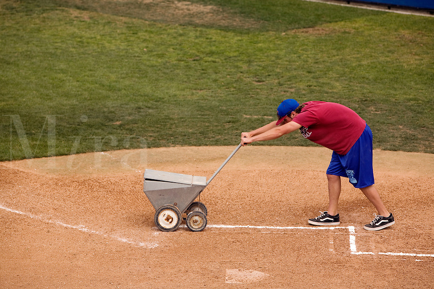 Lining a baseball diamond with lime.