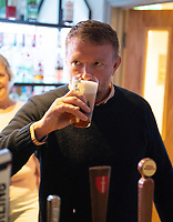 BNPS.co.uk (01202) 558833. <br /> Pic: DanPitmanPhotography/BNPS<br /> <br /> Pictured: Guy samples his 'Gritchie' beer in the clubhouse. <br /> <br /> Hollywood director Guy Ritchie was the unlikely guest of honour at the opening of a community football pitch in a small market town.<br /> <br /> The Lock, Stock and Two Smoking Barrels director signed autographs and chatted with parents and children at the unveiling of the £500,000 artificial pitch in Shaftesbury, Dorset.<br /> <br /> The local team, Shaftesbury FC, are stocking his 'Gritchie' beer made at his brewery in Ashmore, five miles away.