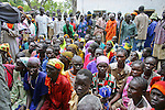 In Rumbek, South Sudan, hundreds of women wait in line to access malaria-preventing mosquito nets on Africa Malaria Day from the international NGO, Population Services International (PSI).