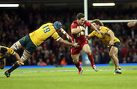 Pictured: George North of Wales (C) is tackled by James Hornwill (L) and Michael Hooper (R) of Australia. Saturday 08 November 2014<br />