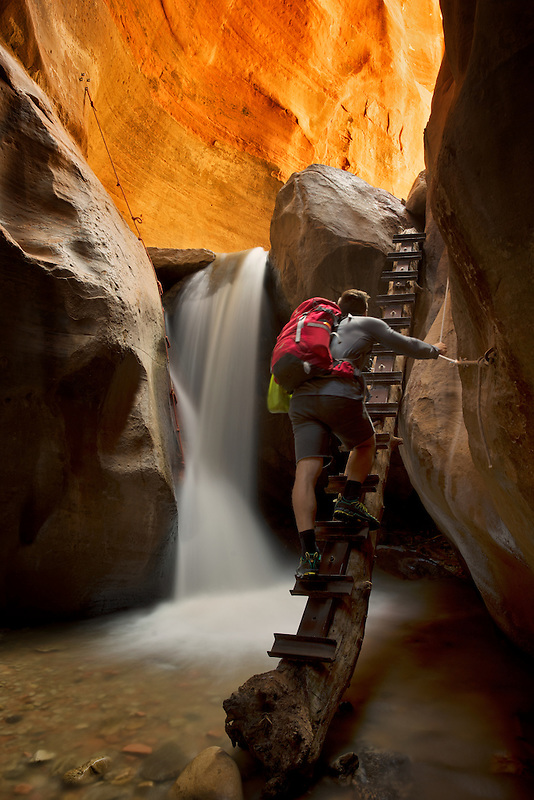 Kanarra Creek Canyon with hiker and waterfall. Utah. Dixie National Forest